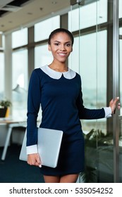 Young afro business woman in blue dress standing with laptop in hand in office