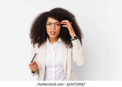 Young afro business woman holding a credit car isolated Young afro business woman holding a credit carshowing a disappointment gesture with forefinger.