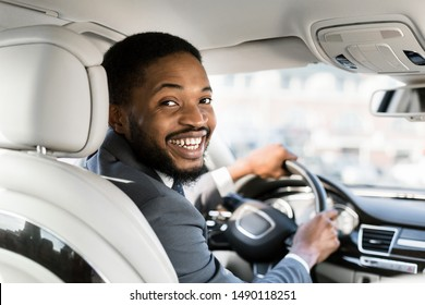 Young afro businessman at driver's seat smiling to camera over shoulder, free space