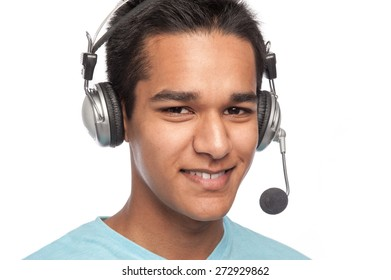 Young afro caribbean man smiling with telephone headset. Studio white background.