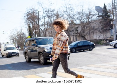 young afro curly woman, walking a street intersection  crosswalk, wearing grey jeans , orange jacket and green  bag