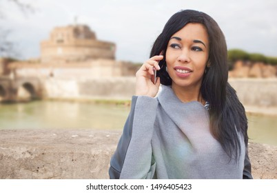 Young afro girl with long hair speaking at phone with her friend in the city - Beautiful girl with dark skin and long hair taking a walk outside and speaking on the phone with her boyfriend