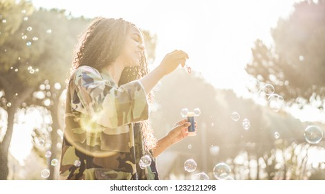 Young afro hair woman blowing soap bubble in city park with back sun light - African happy girl having fun outdoor - Happiness, trend and millennial generation concept - Focus on female left hand