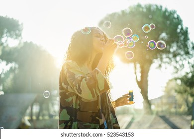 Young afro hair woman blowing soap bubble in city skate park with back sun light - Portrait of african happy girl having fun outdoor - Happiness concept - Focus on face - Warm filter