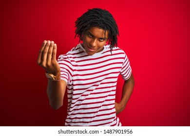 Young afro man with dreadlocks wearing striped t-shirt standing over isolated red background Doing Italian gesture with hand and fingers confident expression