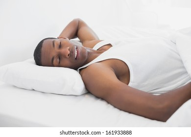 Young Afro man sleeping in bed at home