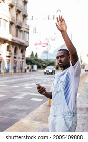 young afro man standing on the street and raising arm to call to attention of a cab. He is holding a smart phone on his other hand. Concept of taxi application