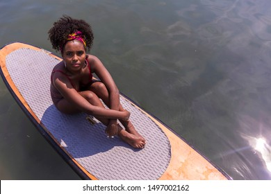Young afro slim girl sitting on paddle Board in sea.