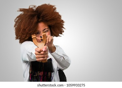 young afro woman holding a slingshot
