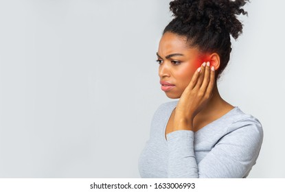 Young afro woman suffering from acute ear pain, touching her ear, grey background, copy space