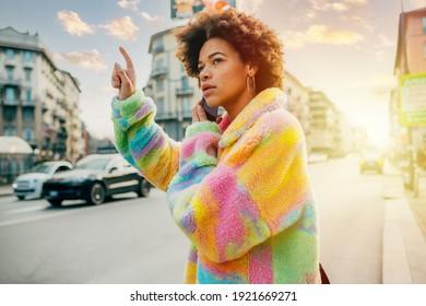 Junge Afro-Frau, die Smartphone-Hosting-Taxifahrer Taxis in der Stadtlampe