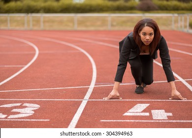Young Afro-American Businesswoman Looking at the Camera While in a Start Position on Race Track.