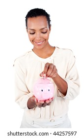 Young Afro-american businesswoman saving money in a piggybank against a white background