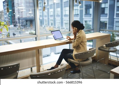 Young afroamerican executive making remote job being in business trip sitting at table in coworking space talking on the phone with entrepreneur using laptop computer with mock up screen with wifi