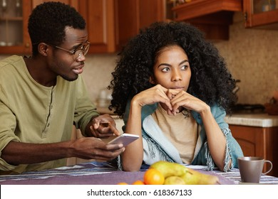 Young Afro-American family fighting in kitchen because of an affair. Man in glasses holding mobile phone, pointing finger at screen, trying to explain himself for love messages from unknown woman