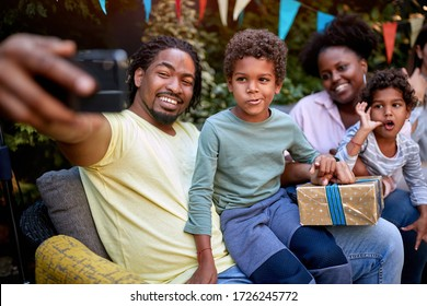young afro-american family gathered at birthday party taking selfie. togetherness