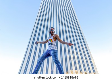 Young afro-american gay man with mobile phone in business buildings area with gay flag