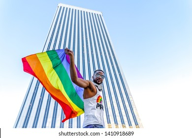 Young afro-american gay man with gay pride flag in business buildings area on wall street of New York