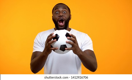 Young Afro-American male with soccer ball emotionally cheering for national team