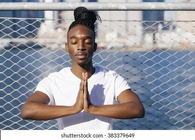Young afroamerican man sitting in meditation outdoors, in New York city.