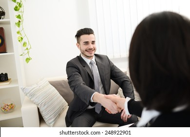 young agent salesman shaking hands at a customer home