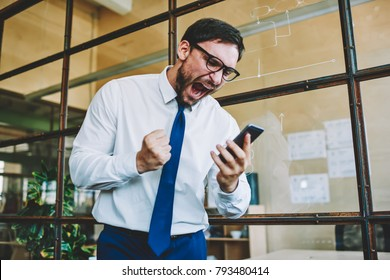 Young aggressive male trader emotionally reacting to online change in financial market and screaming during watching on telephone.Angry man shouting to smartphone while watching football match