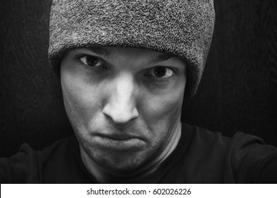 Young agressive Caucasian man in gray hat. Close-up studio face portrait over dark wooden wall background, selective focus, black and white photo