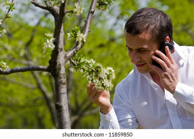 Young agronomist examining the trees in an orchard, while talking on mobile phone