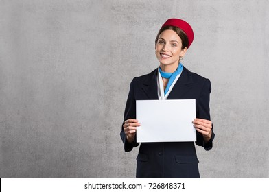 Young air hostess holding white placard isolated on grey background. Flight assistant holding blank sign and looking at camera. Woman stewardess with empty board and copy space.