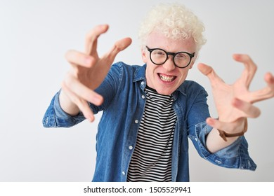 Young albino blond man wearing denim shirt and glasses over isolated white background Shouting frustrated with rage, hands trying to strangle, yelling mad