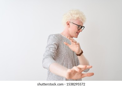 Young albino blond man wearing striped t-shirt and glasses over isolated white background disgusted expression, displeased and fearful doing disgust face because aversion reaction. With hands raised