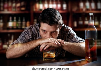 young alcoholic drunk man thoughtful about alcohol addiction drinking indoors at bar of an irish pub leaning hands on whiskey glass in alcoholism concept