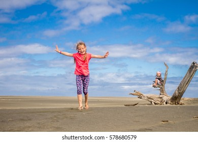 young alone child girl sitting on dry wooden log on dark sand beach