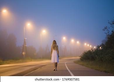 Young alone woman in white dress slowly walking on long sidewalk under street lights in dark summer night. Peaceful moment. Spending time alone. Back view.