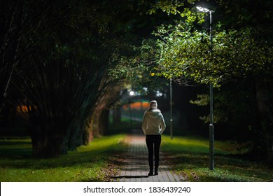 Young alone woman in white jacket walking on sidewalk through alley of trees under lamp light in autumn night. Spending time alone in nature. Peaceful atmosphere. Back view.