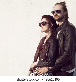 Young alternative couple on a rooftop.  Bikers lovers. Hipsters love. Rock style. Vintage caferacer.