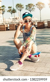 Young alternative girl skater wearing cap and sunglasses sitting on penny board on the city street looking aside playful