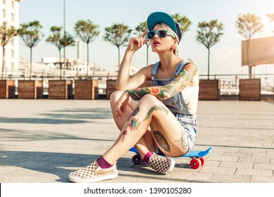 Young alternative girl skater wearing cap and sunglasses sitting on penny board on the city street looking up cool