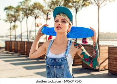 Young alternative girl skater wearing cap standing on the city street holding penny board behind neck looking camera sensual close-up