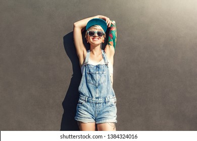 Young alternative girl wearing cap and sunglasses standing isolated on grey wall on the city street hands up relaxed smiling cheerful