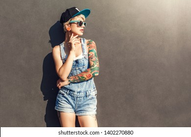 Young alternative girl wearing cap and sunglasses standing isolated on grey wall on the city street looking aside posing sensual
