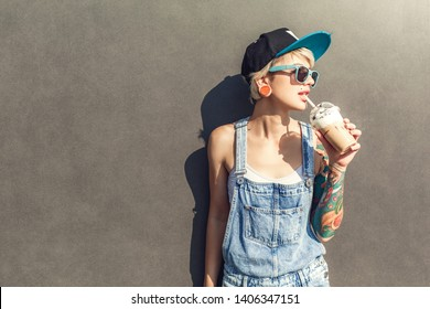 Young alternative girl wearing cap and sunglasses standing isolated on grey wall on the city street holding cup drinking iced coffee looking aside smiling joyful