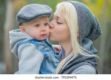 A young alternative mother is in a park with her baby boy in the fall. They are dressed warmly. The mother is holding her son and kisses him on the cheek.