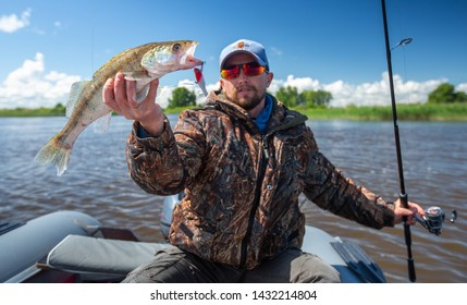 Young amateur angler holds the fish (Zander) in the hand being on the lake