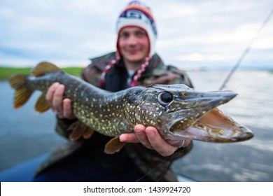 Young amateur angler holds the Pike fish (Esox lucius) in his hands being on the lake. Focus on the fish only (in area near its eye)