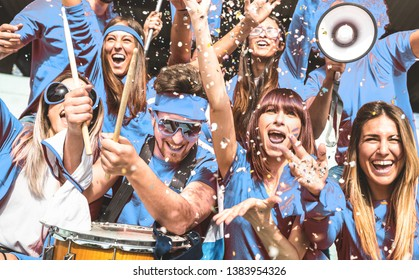 Young amateur football fan supporters cheering with flags watching local soccer cup match at stadium - Friends people group on blue t shirts having excited fun on sport world championship final