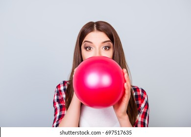 Young amazed brown-haired girl is blowing red balloon for birthday party and looking at the camera on a grey background