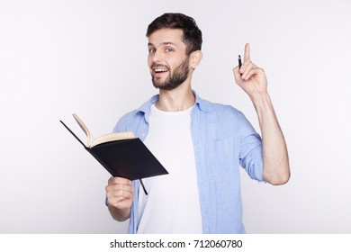 Young amazed Caucasian man with notebook looking at camera with opened mouth showing teeth, pointing his finger at white background with copy space for your advertisement or promotional information.