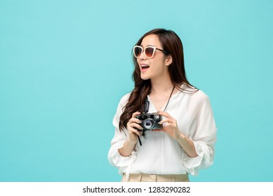 Young amazed female asian in casual attire holding a camera in sky blue background
