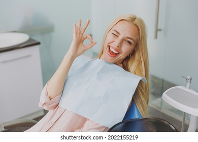 Young amazed smiling happy woman covered by napkin show ok gesture sit at dental office chair indoor light modern cabinet waiting stomatologist for oral procedure. Healthcare caries enamel treatment